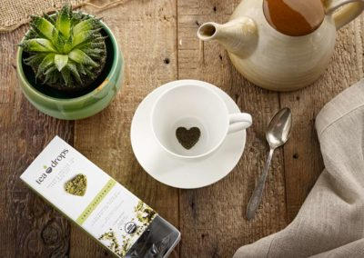 Tea Drops product photography featuring tea drop and tea pot on wood